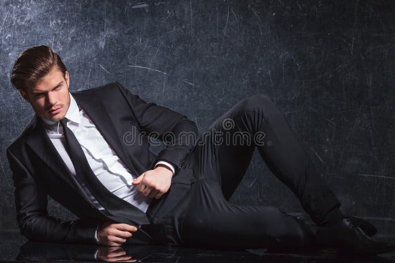 Sexy junger Modemann, der sich hinlegt lizenzfreies stockfoto