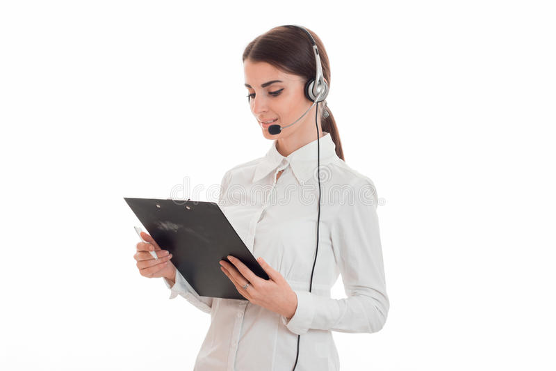 Sexy junges Call-Center-Büromädchen mit den Kopfhörern und Mikrofon, die Brett mit Dokumenten in ihren Händen lokalisiert betrach lizenzfreies stockfoto