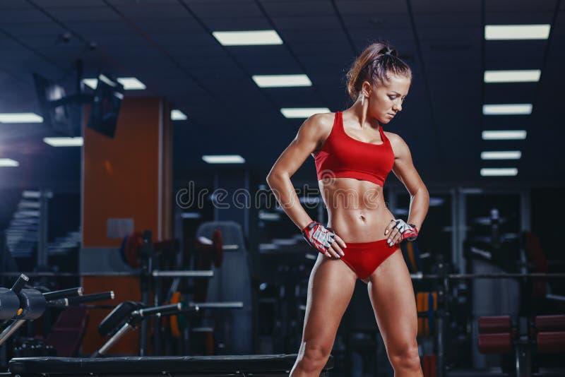 sexy junges Leichtathletikmädchen, das nach Eignungstraining in der Turnhalle stillsteht lizenzfreie stockfotos