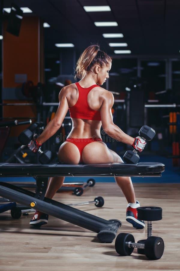 Sexy junges Leichtathletikmädchen mit perfektem nehmen Sitz mit Dummköpfen in der Turnhalle ab stockfotografie