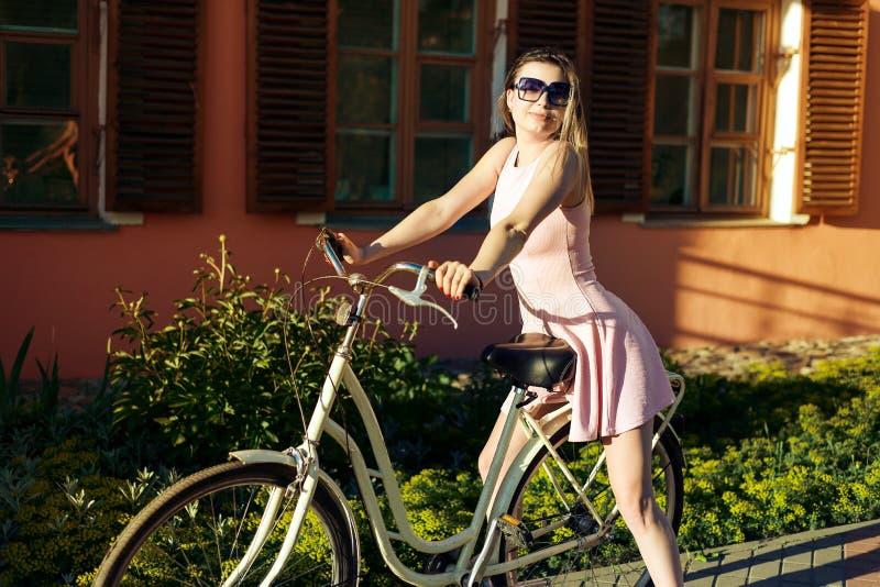 Sexy junges Mädchen auf einem Fahrrad mit den Gläsern und rosa Kleid, die das Porträt sitzt auf dem Sitz aufwirft stockfotografie