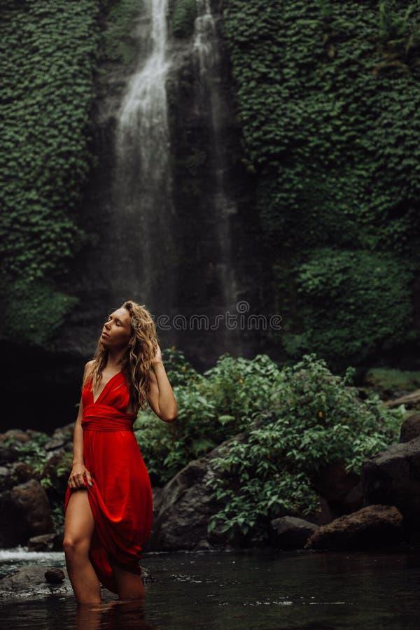 Sexy junges Mädchen im roten Kleid an überraschendem Wasserfall Bali - die beste Kaskade in Indonesien lizenzfreie stockbilder