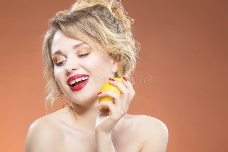 Sexy Kaukasisch Blond Meisje die Geel Citroenfruit bijten Het stellen tegen Oranje Achtergrond royalty-vrije stock foto