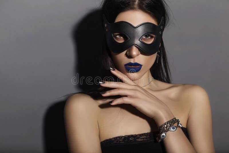 Sexy kaukasische Brunettefrau, die schwarze Spitze, ledernen Katze mas trägt stockbild