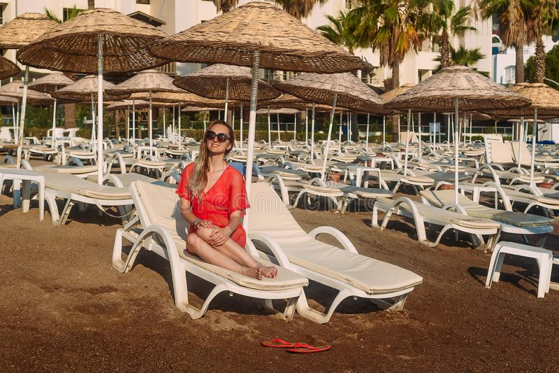 Sexy kaukasische Frau im roten transparenten Strandkittel, der auf einem weißen Ruhesessel auf dem Strand liegt stockbilder