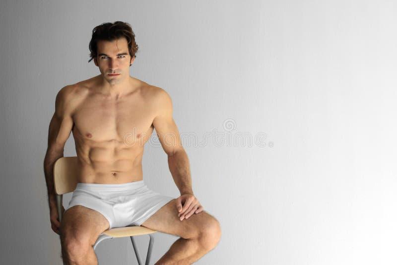 Sexy kerel op kruk stock fotografie