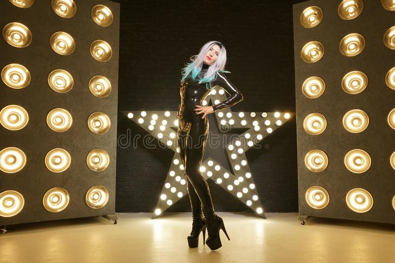 Hot slim woman posing in latex rubber fashion clothes on black background with yellow lights bulbs stock photo