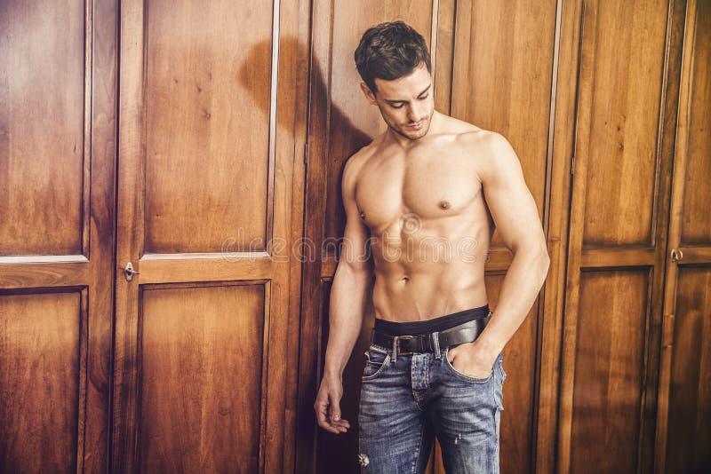 Sexy knappe jonge mens die zich shirtless tegen garderobe bevinden stock foto