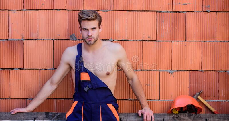 Sexy laborer. Attractive worker. Handsome man wear overalls. Construction. Worker brick wall background. Perform basic royalty free stock photos