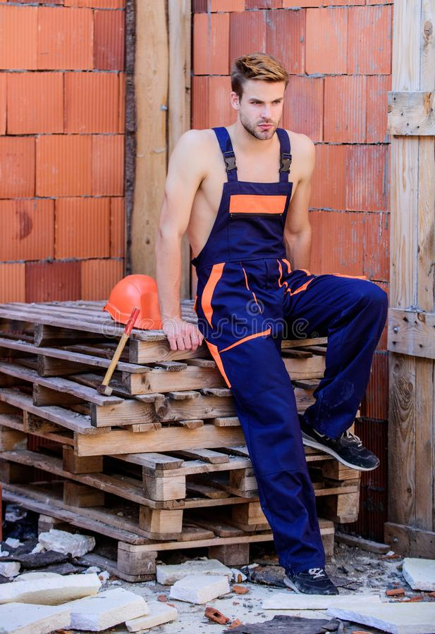Sexy laborer. Building construction. Worker brick wall background. Man build own house. Perform basic tasks. Masculinity stock photo
