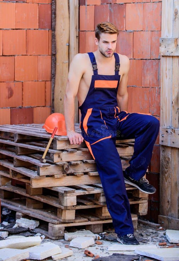 Sexy laborer Costruzione di edifici Sfondo parete mattone lavoratore L'uomo costruisce la propria casa Esecuzione di attività di  fotografia stock