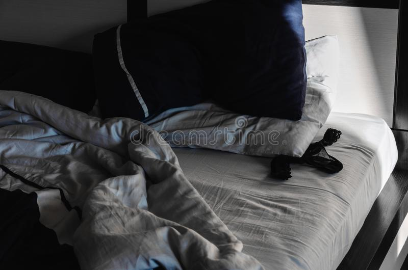 Sexy lace black women`s panties on crumpled bed. Morning after a hot night. Background for sexual concept.  stock photos