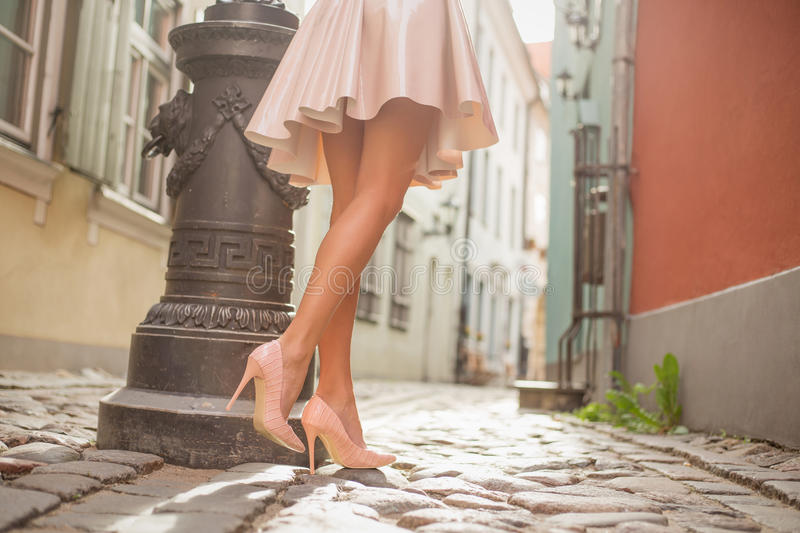 lady with beautiful legs walking in old town stock images
