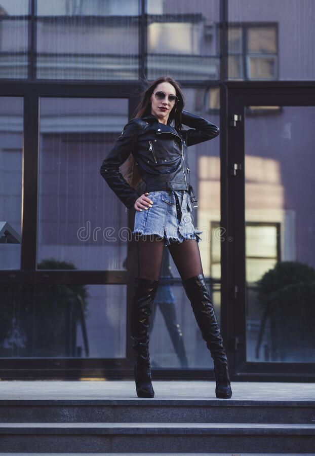 Sexy lady with long legs. Posing in leather jacket. Fashion look royalty free stock images