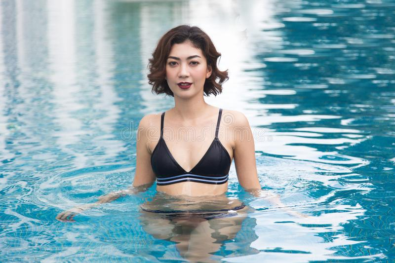 Lady in swimming suite posting water pool. Relax in holiday concept stock photos