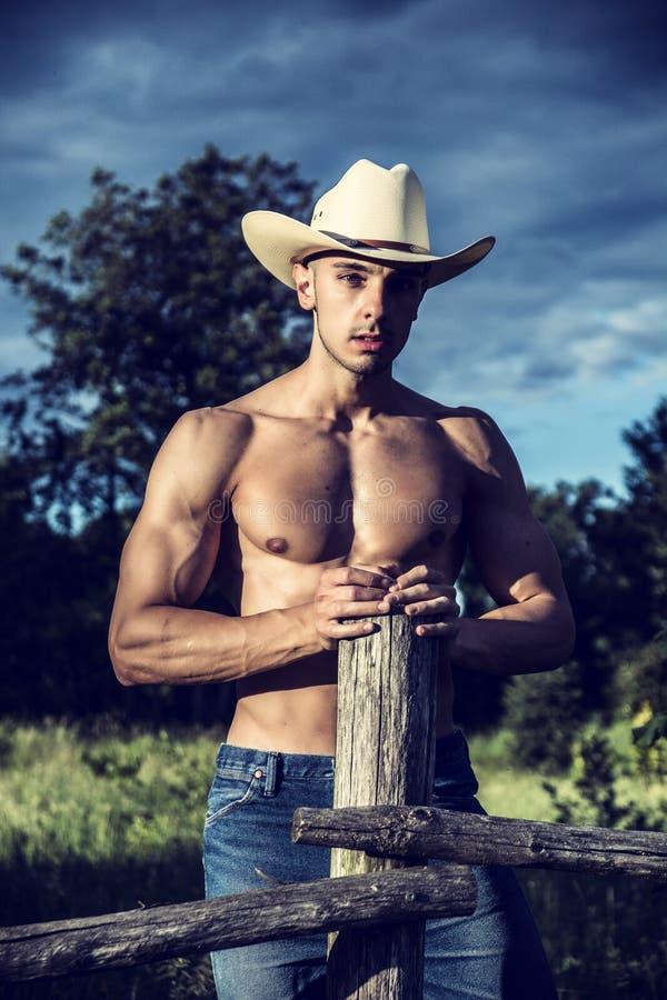 Sexy Landwirt oder Cowboy nahe bei Heufeld lizenzfreie stockfotografie