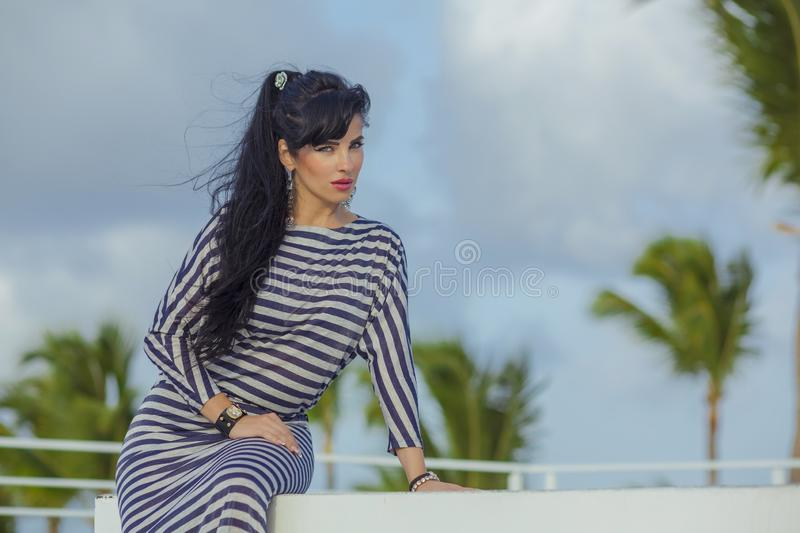 Sexy latina with long black hair at the top terrase overlooking the palm trees. Sexy latina with long black hair in stripped dress royalty free stock images