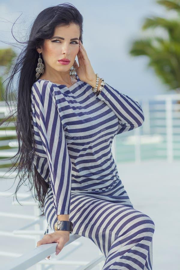 Sexy latina with long black hair at the top terrase. Sexy latina with long black hair in stripped dress stock image