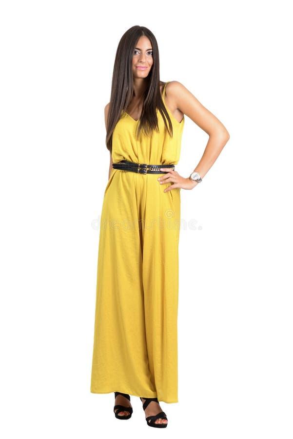 Sexy Latino mannequin in gele avond die jumpsuit aan camera stellen stock afbeeldingen
