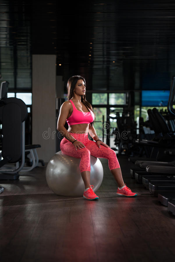 Latino Woman Resting After Workout In Gym. Young Mexican Woman Resting On Ball After Working Out In Fitness Cente stock photography