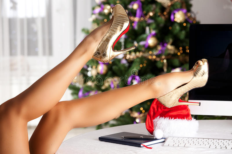 Legs. Beautiful tanned female lags in high heels, holding over the table royalty free stock photography