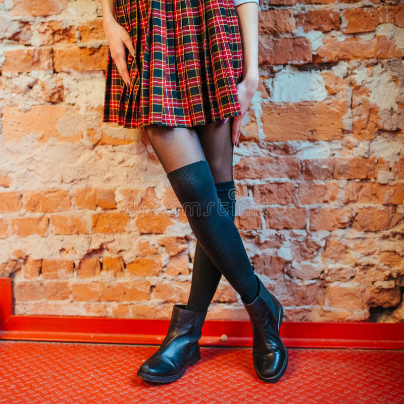 legs of a girl in skirt and black boots stock images