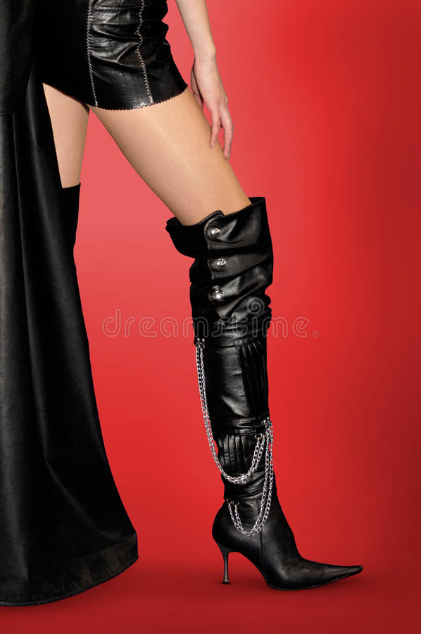 Legs and Stiletto Boots. Woman in leather outfit and black leather high stiletto boots Isolated on red background with clipping path royalty free stock photography