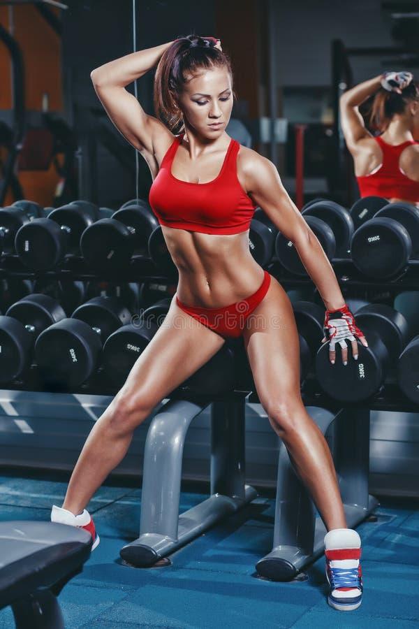 Sexy Leichtathletikfrau der Eignung in der roten Kleidung, die auf Dummkopfreihe in der Turnhalle sitzt stockbild