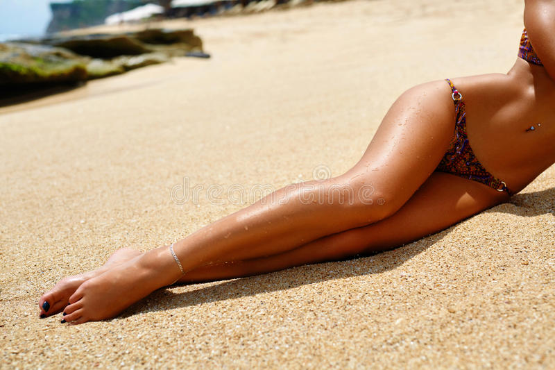 Long Woman Legs Sunbathing On Beach Sand. Body Part. Woman Legs On Beach. Beautiful Girl With Slim Fit Body, Healthy Smooth Silky Sun Tanned Skin And Long stock image