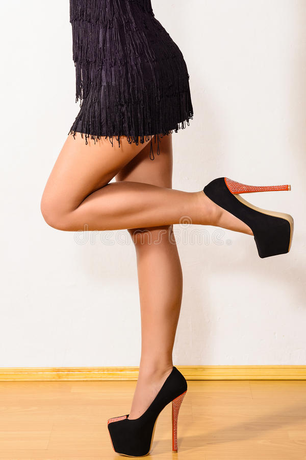 Long woman's leg and high heel shoes. On wooden flour stock photography