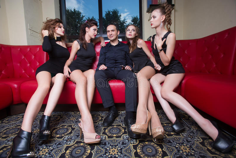 Sexy lovelace Mann umgeben durch den heißen Frauenwunsch lizenzfreie stockbilder