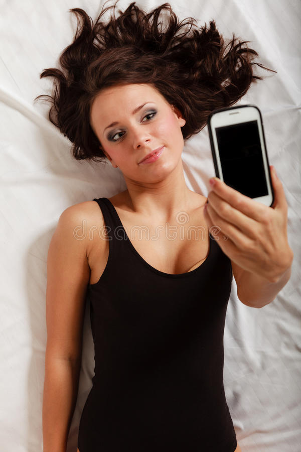 Sexy lui meisje die met telefoon op bed in slaapkamer liggen royalty-vrije stock foto