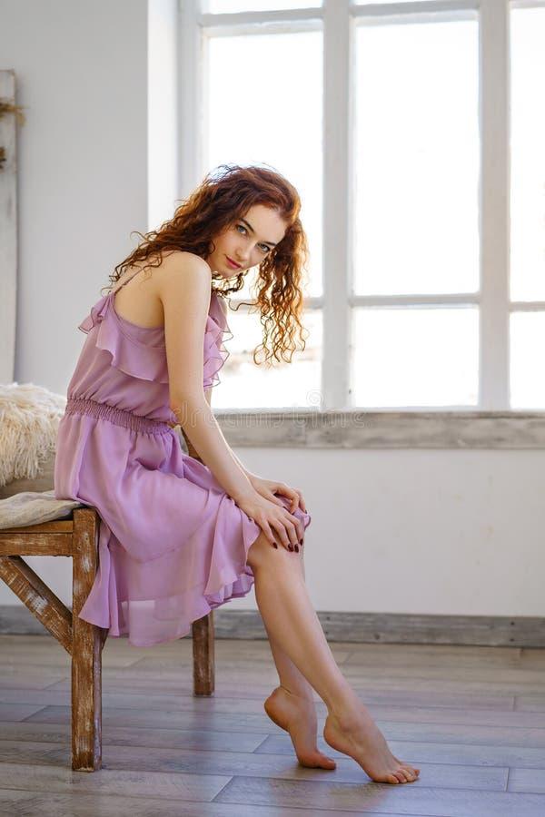 Luxurious woman in address. Fashion redhead in beautiful dress posing sitting in Studio. Beautiful hair and a perfect girl fi. Gure royalty free stock photography