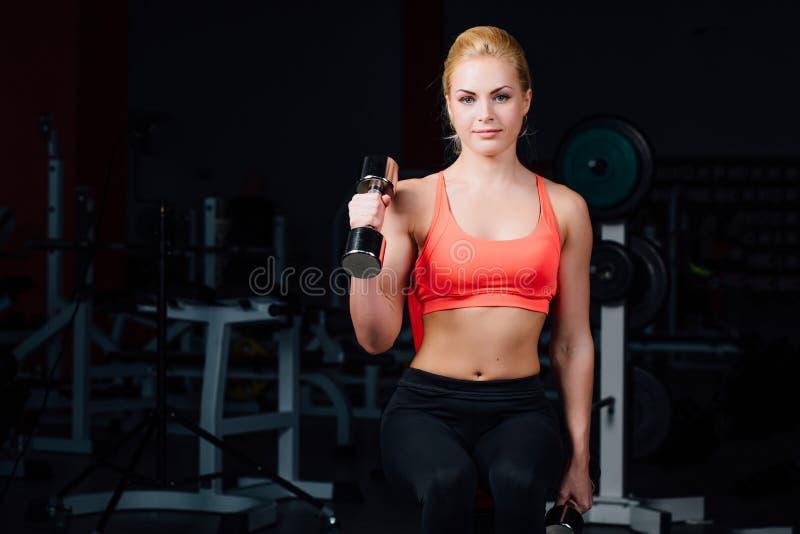 Sexy Mädchen, das Übungen in ihren Armen Bizeps und Trizeps tut Eignung mit Dummköpfen in der Turnhalle stockfotos