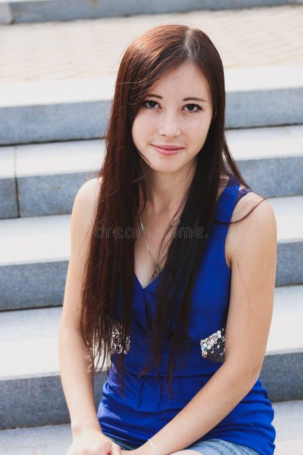 Sexy Mädchen, das auf der Treppe im Park sitzt stockfotografie