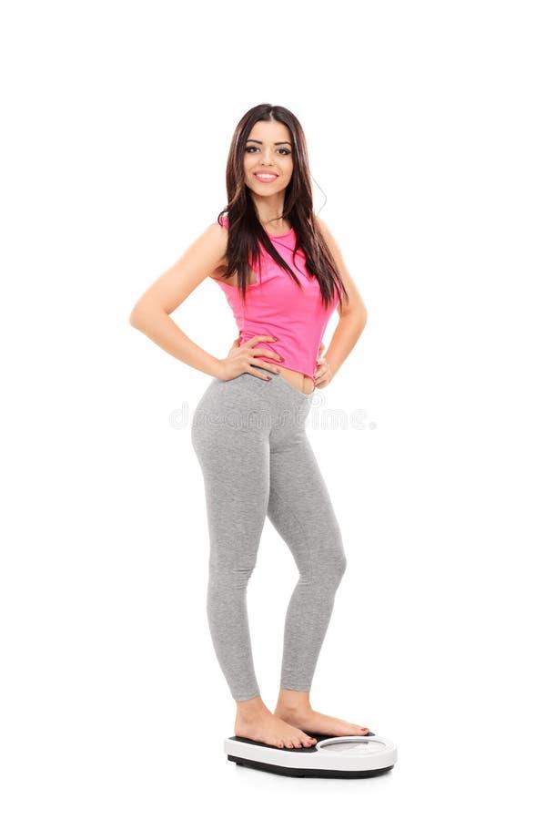 Sexy Mädchen, das auf einer Gewichtsskala steht lizenzfreie stockfotografie