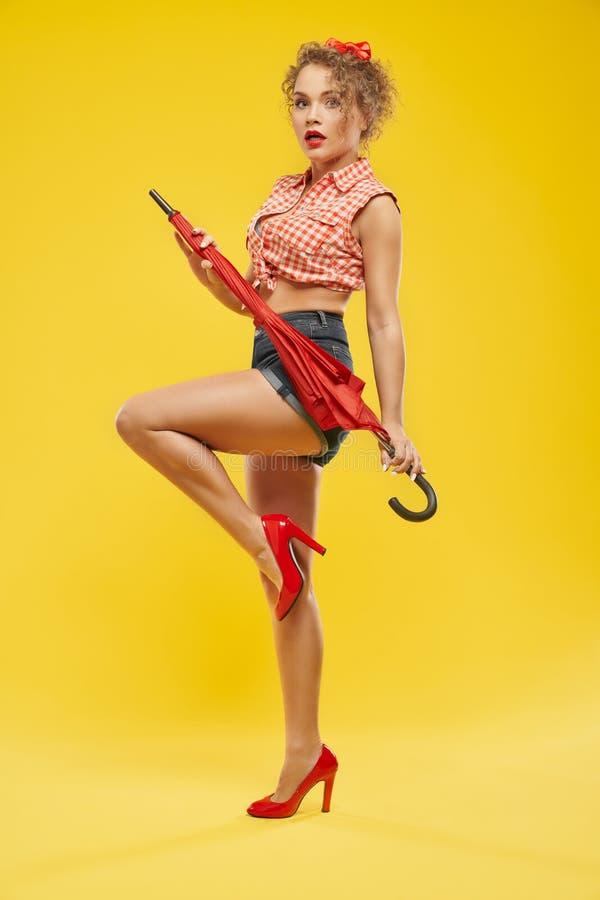 Sexy Mädchen in den roten Schuhen auf den Fersen, die mit rotem Regenschirm aufwerfen lizenzfreie stockfotografie