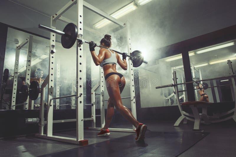 Sexy Mädchen der Eignung in der Turnhalle, die Hocke auf Rauchhintergrund tut lizenzfreie stockfotografie