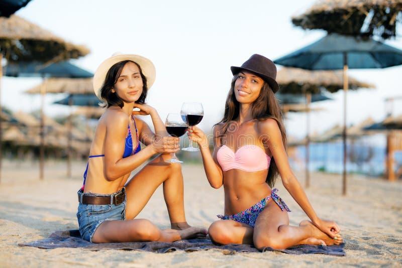 Sexy Mädchen, die einen Wein auf einem Strand essen lizenzfreie stockbilder