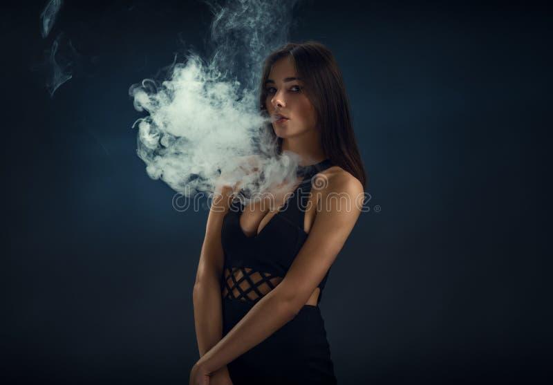 Sexy Mädchen in einem schwarzen Kleid, das elektronische Zigarette raucht lizenzfreie stockbilder
