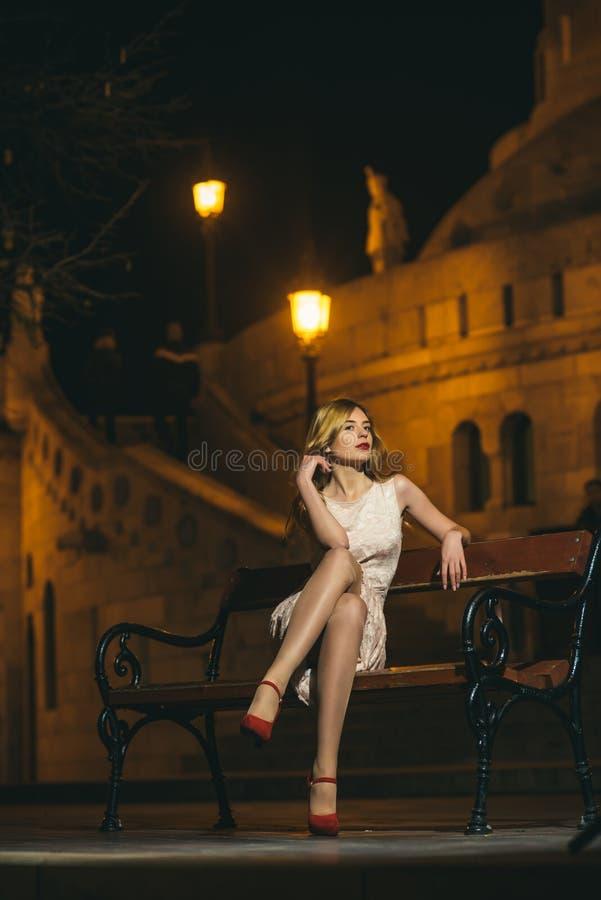 Sexy Mädchen im eleganten Kleid sexy Mädchenrest auf Bank stockfotos