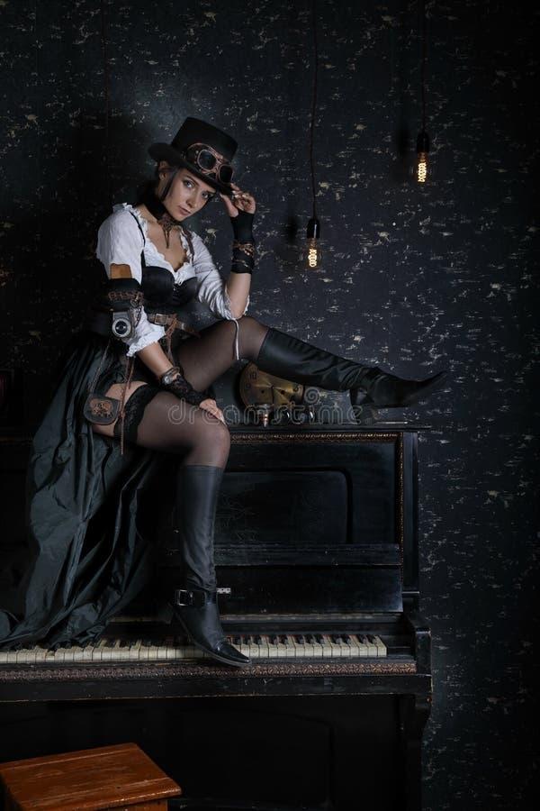 Sexy Mädchen steampunk, das zuhause auf Klavier sitzt lizenzfreie stockfotografie