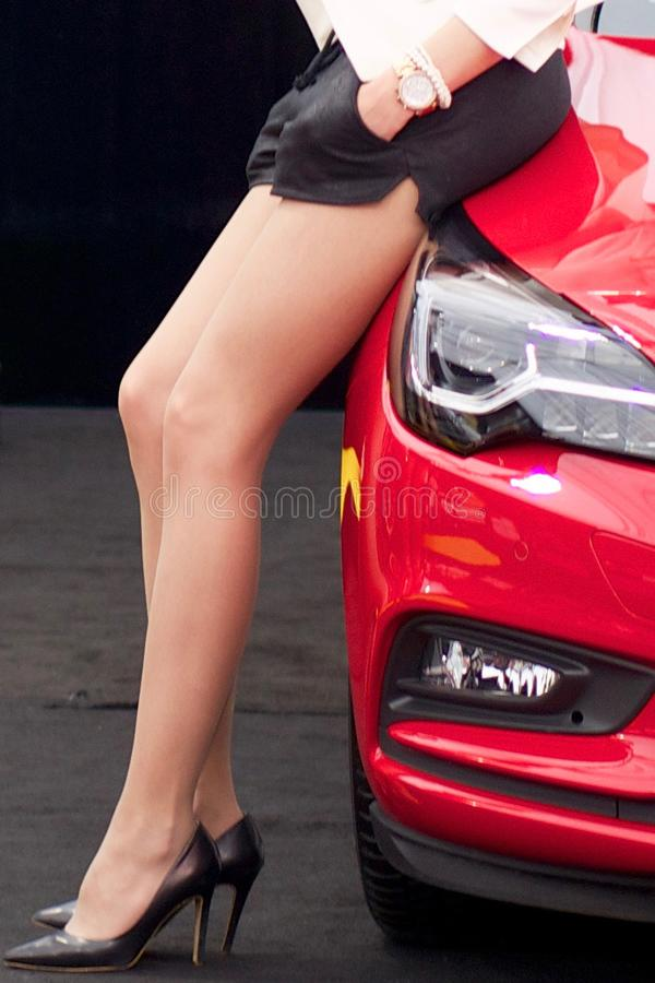Sexy Mädchenbeine, welche die hohen Absätze und Minirock, sitzend auf Auto tragen lizenzfreie stockfotografie