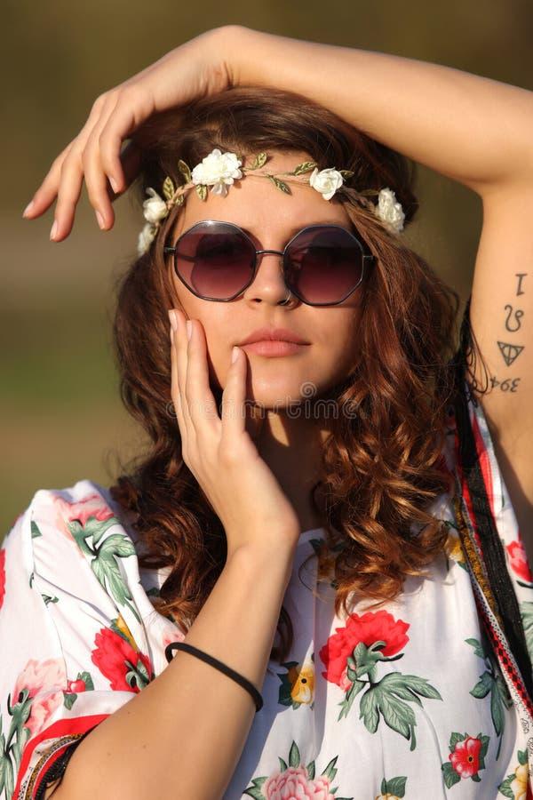 Sexy Mädchenhippie in der Sonnenbrille, welche die Kamera betrachtet und Händchenhalten stellt draußen gegenüber lizenzfreies stockbild