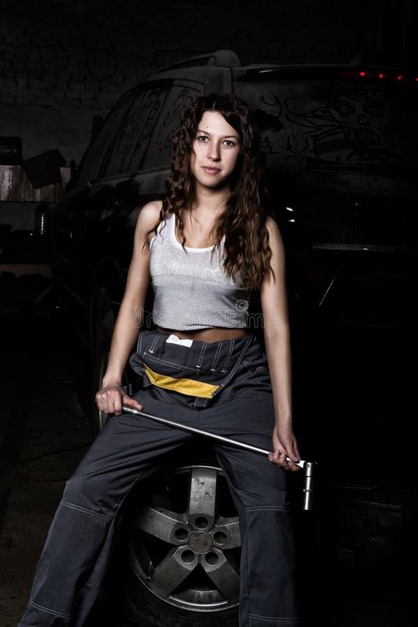 Sexy Mädchenmechaniker, der auf einem Reifen hält einen Schlüssel in seiner Hand sitzt farbloses Lebenkonzept lizenzfreie stockbilder