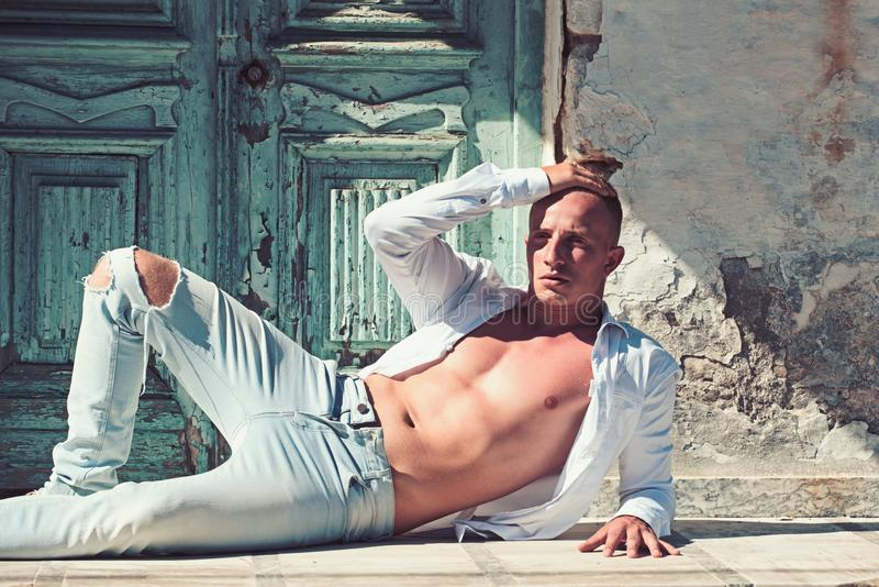 Macho man with bare chest and muscular torso relax at wooden door. fashion model in jeand and shirt. summer. Vacation and relax. muscular athlete of sportsman royalty free stock photos
