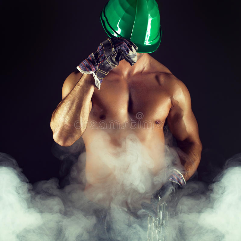 Macho worker in helmet. Gloves and fog royalty free stock photo