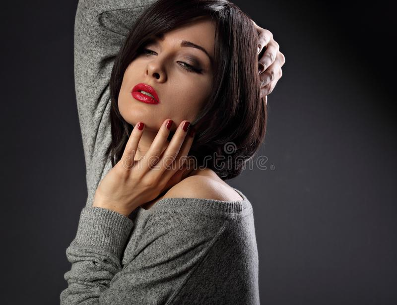 Makeup woman with short bob hair style, red lipstick touchi. Ng her face on dark shadow background. Closeup portrait royalty free stock images