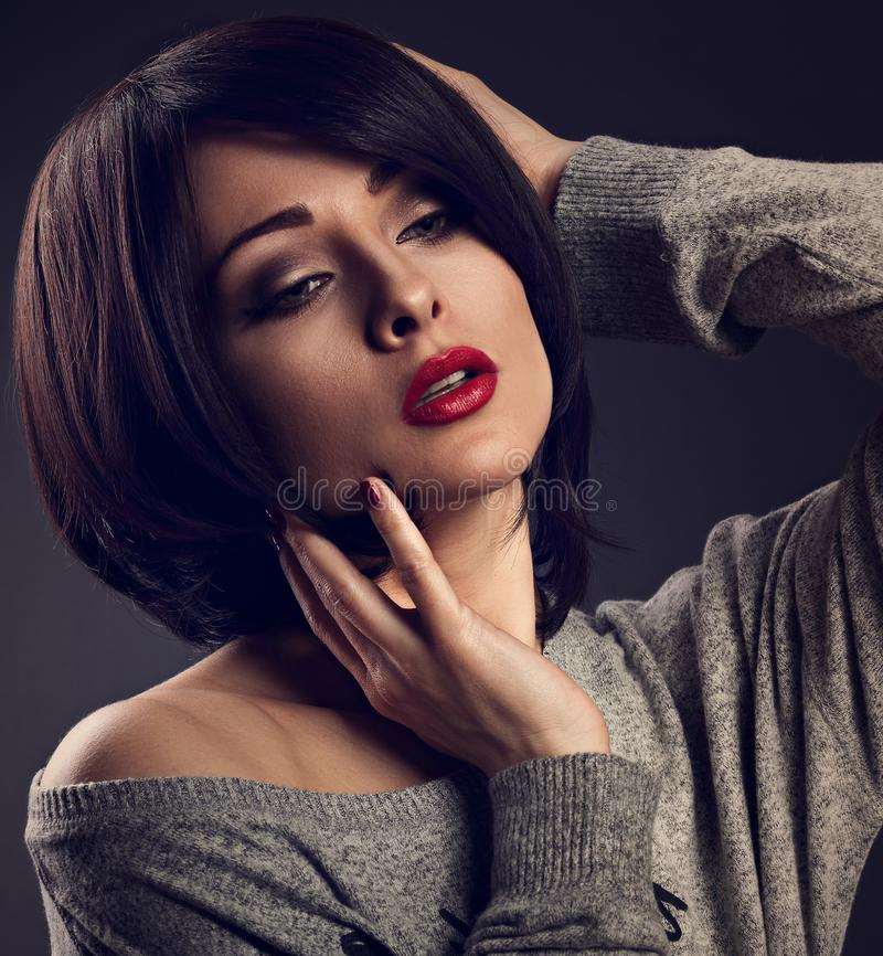 Makeup woman with short bob hair style, red lipstick touchi. Ng her face on dark shadow background. Closeup portrait. Toned royalty free stock photos