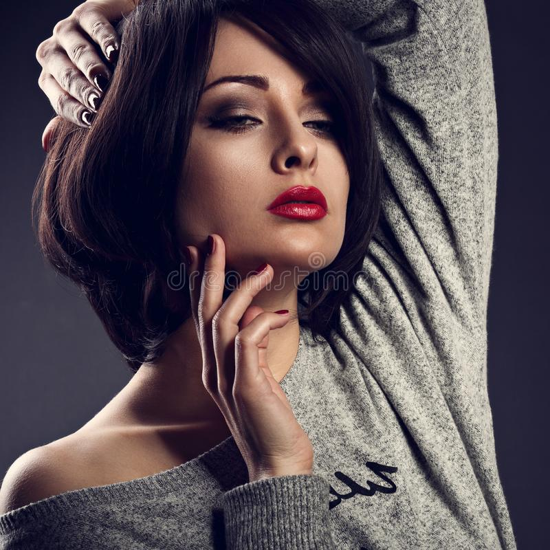 Makeup woman with short bob hair style, red lipstick touchi. Ng her face on dark shadow background. Closeup toned portrait stock photo